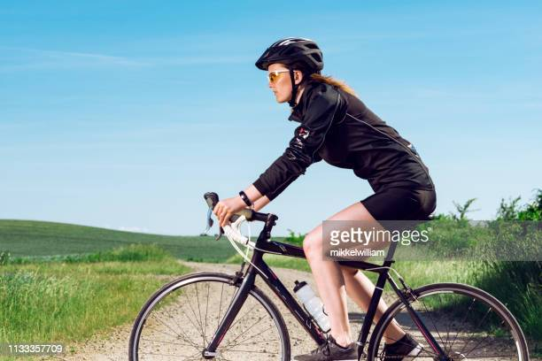 Portrait of female athlete with helmet riding her bicycle on rural road