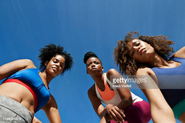 portrait of female athletes in sportswear against blue sky - コイリーヘア ストックフォトと画像