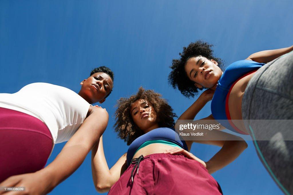 Portrait of female athletes in sportswear against blue sky : Stock Photo