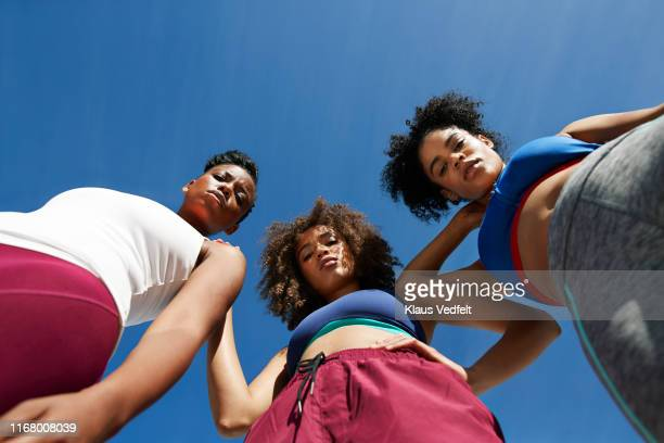 portrait of female athletes in sportswear against blue sky - alleen vrouwen stockfoto's en -beelden