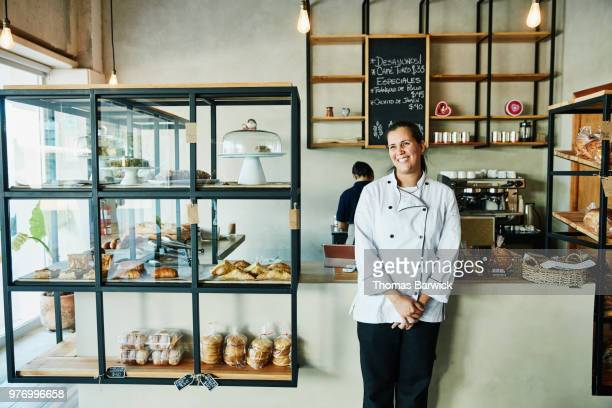 portrait of female bakery owner standing in front of counter in shop - business owner stock photos and pictures