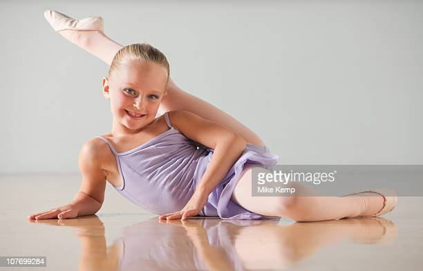 portrait of female ballet dancer (6-7) stretching in dance studio - little girls leotards stock photos and pictures