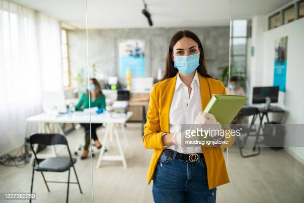 portrait of female bank manager with protective face mask in office - employee stock pictures, royalty-free photos & images