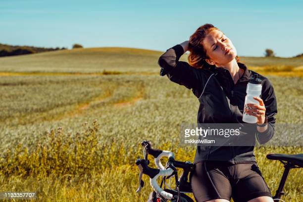 Portrait of female bicycle rider drinking water during a break