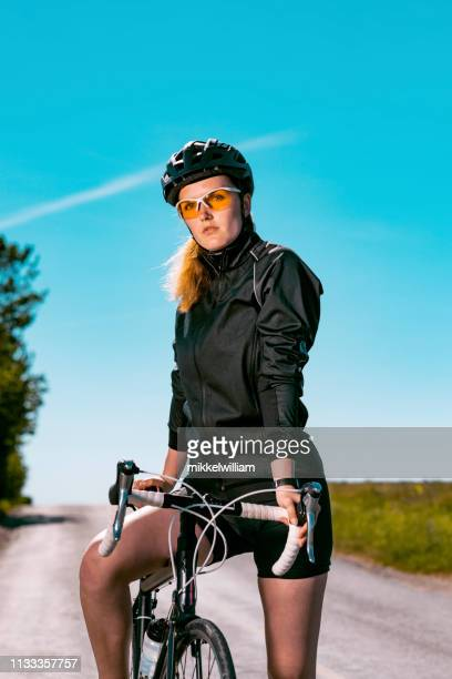 Portrait of female bicycle rider holding on to her bike on road