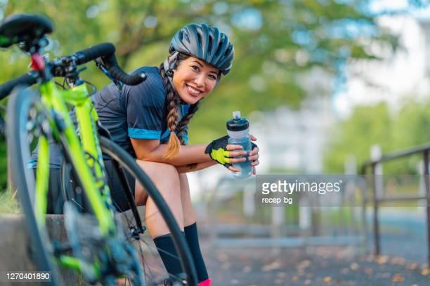 retrato de motociclista sorrindo para câmera em parque público - ciclismo - fotografias e filmes do acervo