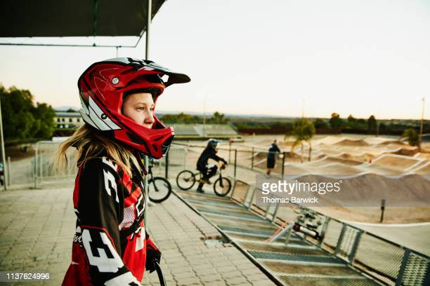 portrait of female bmx racer looking at track before race start - preparation stock-fotos und bilder