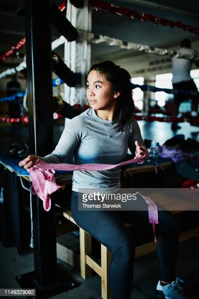 Portrait of female boxer removing hand wraps after workout in boxing gym