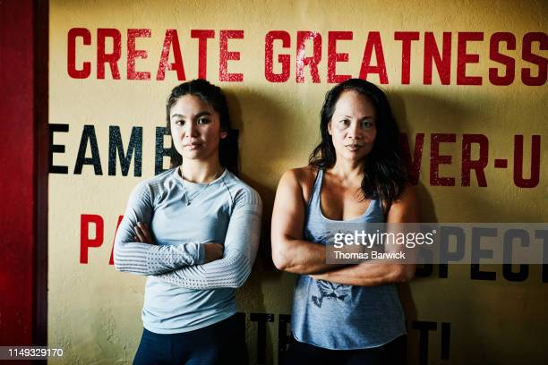 Portrait of female boxers leaning against wall in boxing gym