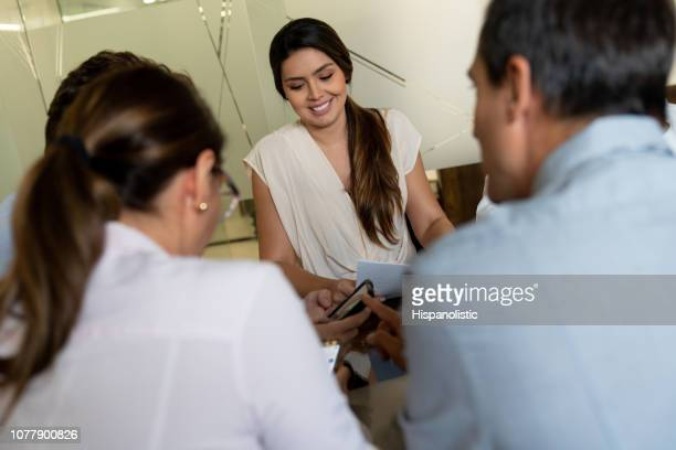 portrait of female business leader in a meeting smiling while listening to colleagues discuss something and looking at a smartphone - hispanolistic stock photos and pictures