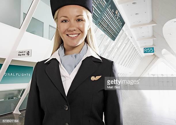 Portrait of female cabin crew member in airport building