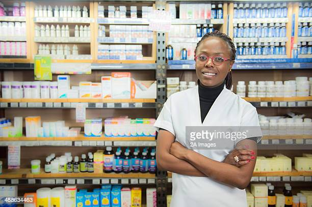 Portrait of female chemist standing in white coat in front of various medications in health store, Johannesburg, South Africa