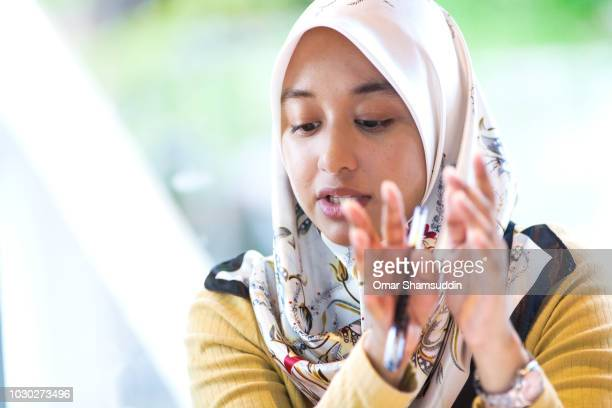 Portrait of female college students in hijab doing a hand gesture