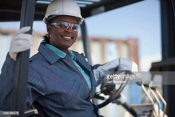 Portrait of female construction worker driving mechanical digger