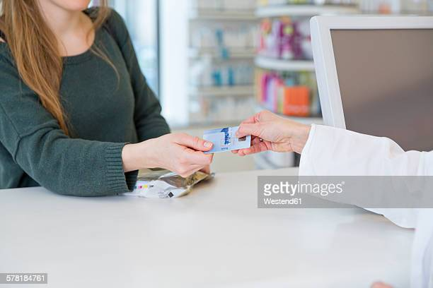 Portrait of female customer paying cashless in a pharmacy