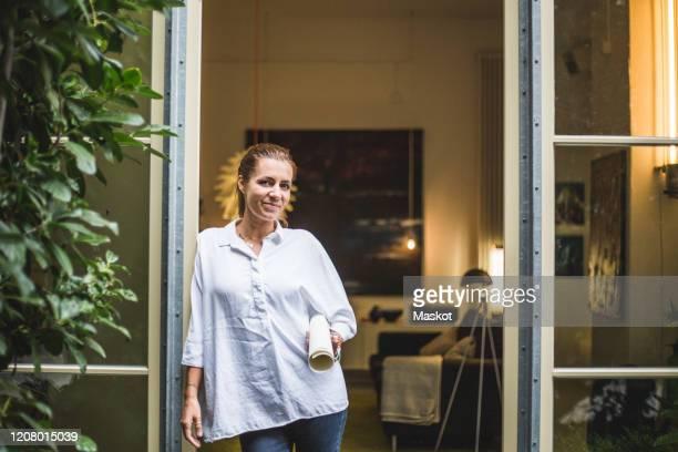 portrait of female design professional standing at house entrance - 女性建築家 ストックフォトと画像
