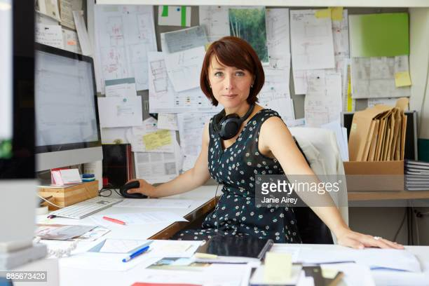 Portrait of female designer at office desk