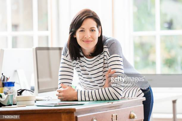 portrait of female designer leaning forward on drawers in creative studio - mid adult woman sweater stock pictures, royalty-free photos & images