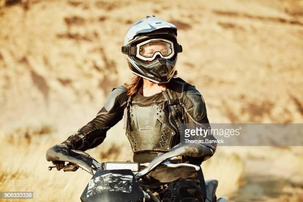 Portrait of female dirt bike rider during desert ride