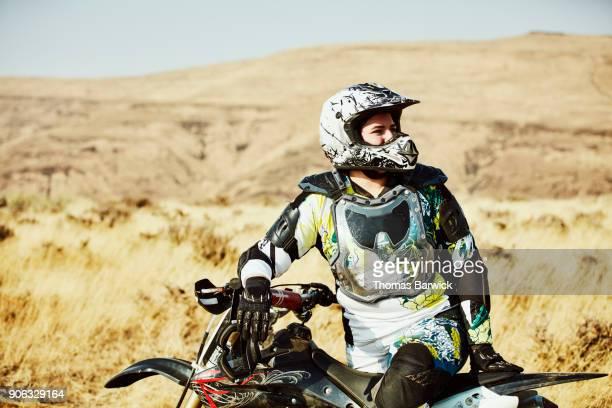 Portrait of female dirt bike rider resting during desert ride