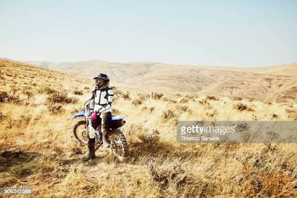 Portrait of female dirt bike rider sitting on bike during desert ride