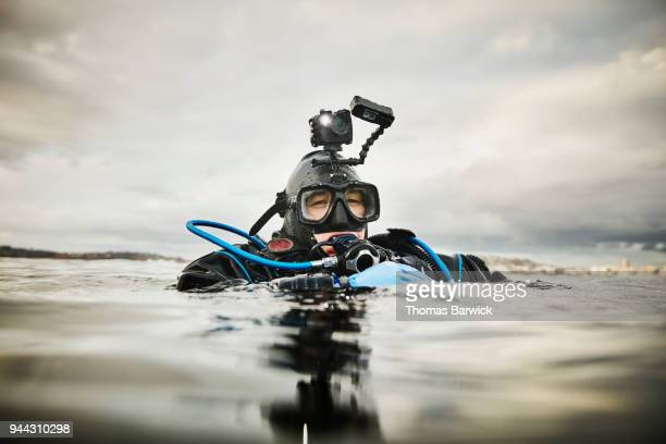 Portrait of female diver at surface of water before descending for open water dive