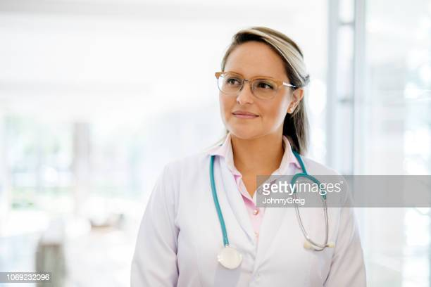 portrait of female doctor looking away from camera - junior doctor stock pictures, royalty-free photos & images
