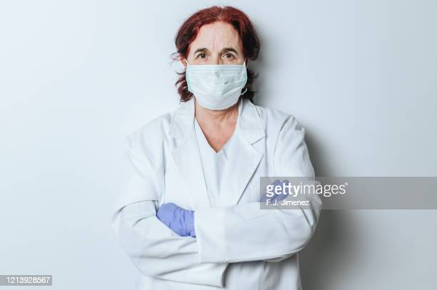 portrait of female doctor with surgical mask - emergencies and disasters stock pictures, royalty-free photos & images