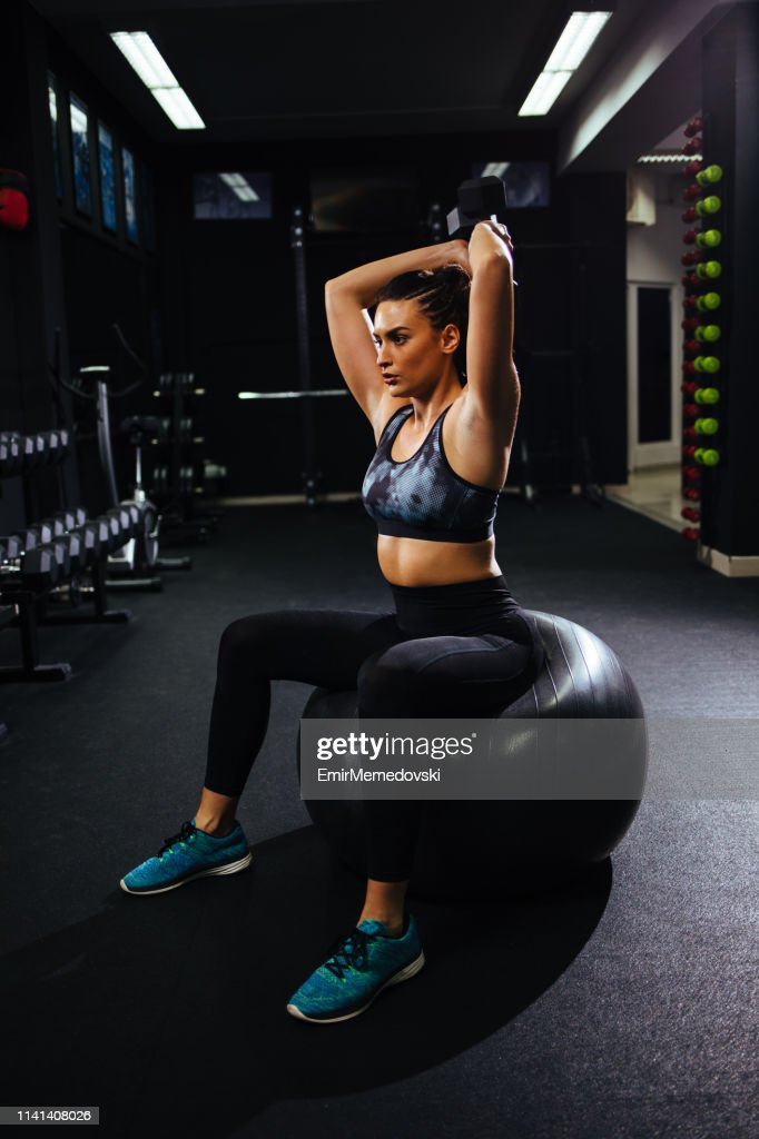Portrait of female doing exercises with dumbbell at gym : Stock Photo