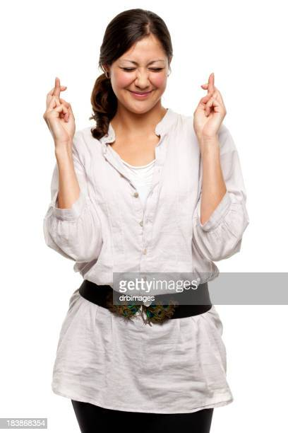 Portrait of female dressed in white crossing her fingers