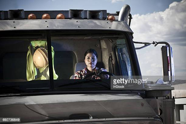 Portrait of female driver driving recycling plant truck