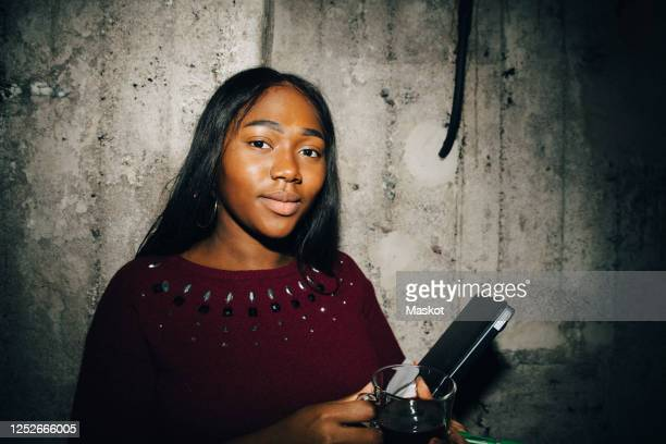 portrait of female entrepreneur with laptop standing against wall at workplace - vanguardians stock pictures, royalty-free photos & images