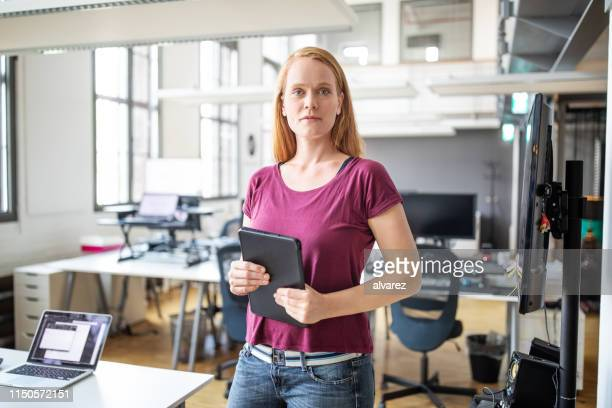 portrait of female executive standing at office - one mid adult woman only stock pictures, royalty-free photos & images