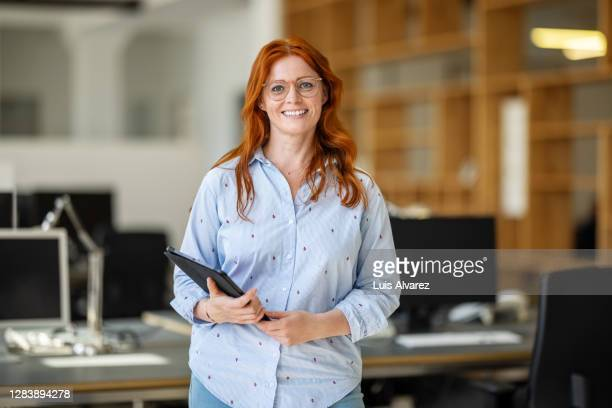portrait of female executive standing at office - dyed red hair stock pictures, royalty-free photos & images