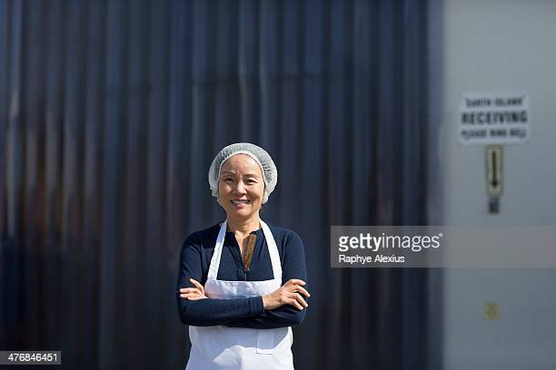 Portrait of female factory worker, arms folded