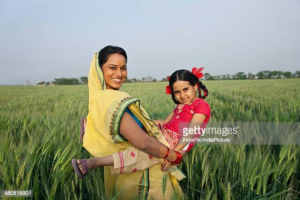 Portrait of female farmer carrying daughter in farm