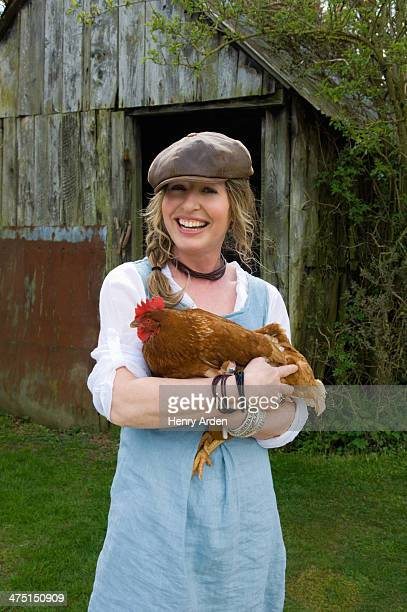 Portrait of female farmer holding hen