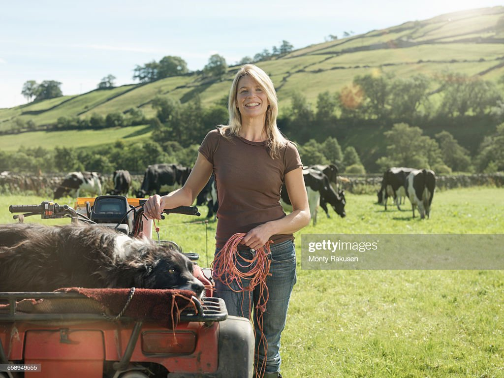 Portrait of female farmer in field with cows : Stock Photo
