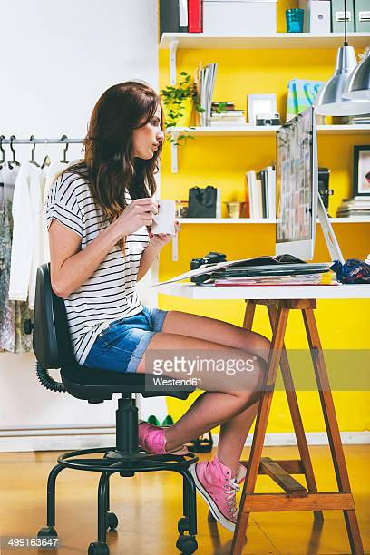 Portrait of female fashion blogger with coffee cup looking at computer in her office