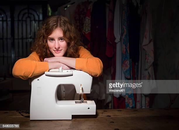 Portrait of female fashion designer leaning on sewing machine at her studio