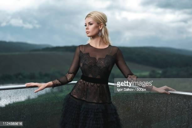 portrait of female fashion model wearing black lace dress leaning on wet railing - viewpoint stock pictures, royalty-free photos & images