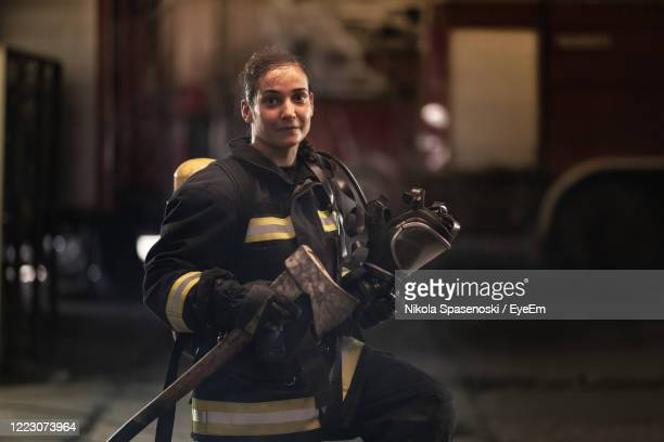 portrait of female firefighter wearing protective workwear holding axe - rescue worker stock pictures, royalty-free photos & images