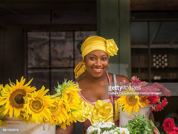 Portrait of female flower seller wearing yellow traditional costume Havana, Cuba