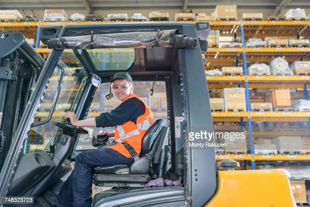 Portrait of female forklift truck driver in train works warehouse