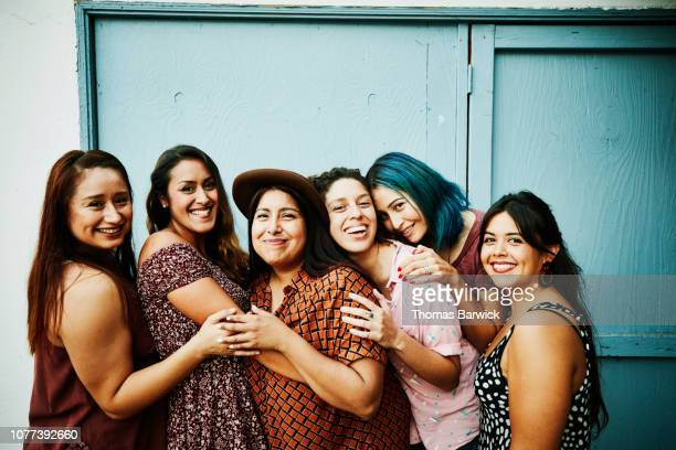 portrait of female friends embracing in front of blue wall - sólo mujeres fotografías e imágenes de stock