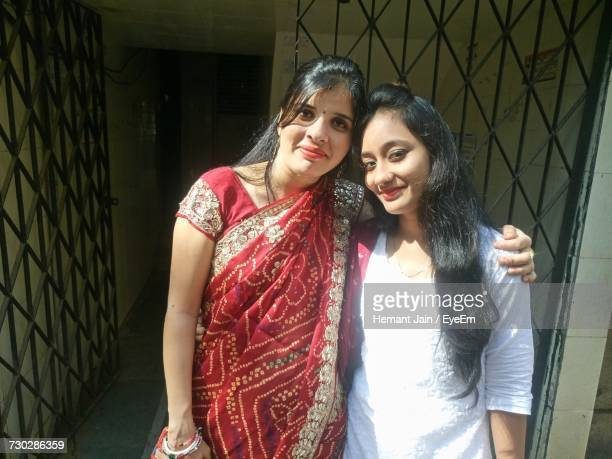 portrait of female friends smiling while standing by gate - salwar kameez stock pictures, royalty-free photos & images