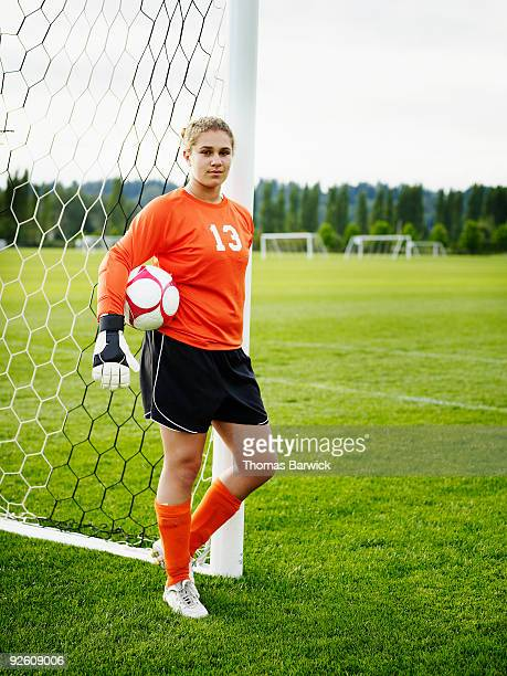 portrait of female goalkeeper leaning against goal - goalkeeper stock pictures, royalty-free photos & images