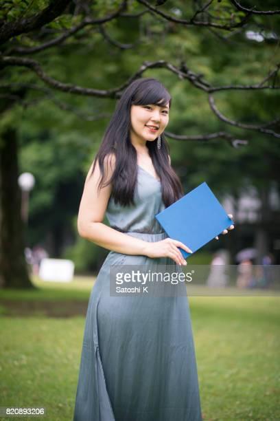 Portrait of female graduate holding diploma in university