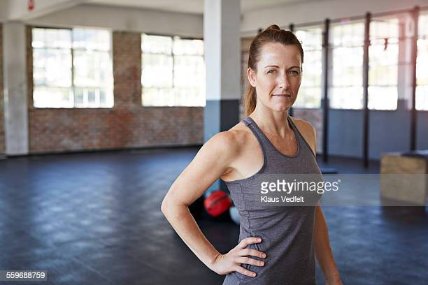 portrait of female gym instructor at gym - handen op de heupen stockfoto's en -beelden