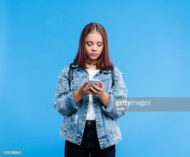portrait of female high school student using smart phone - schoolgirl stock pictures, royalty-free photos & images